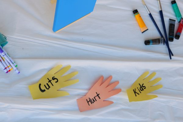 "art supplies and cut outs of hands that reads ""cuts hurt kids"""